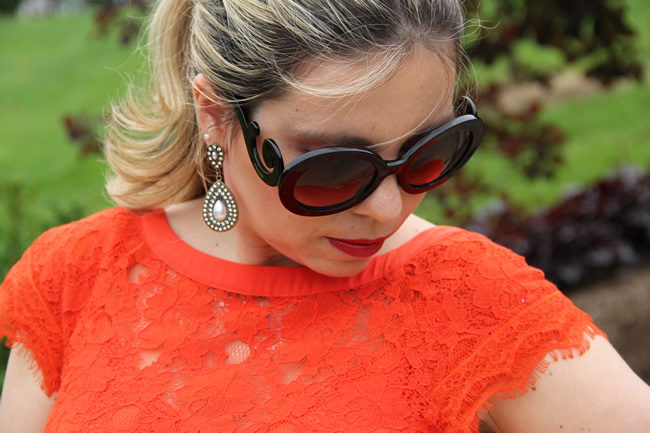 red lace dress and black round prada sunglasses